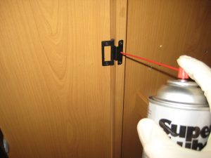 Greasing the cabinet door hinge with Suer Lube Dri Film